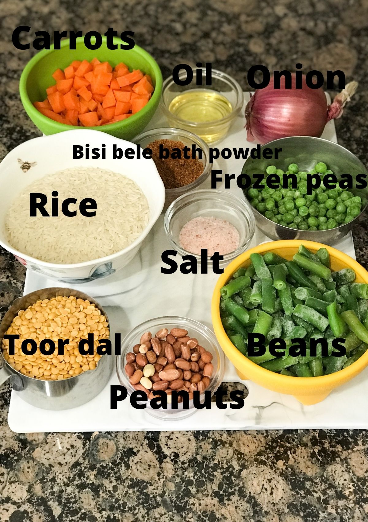 All the ingredients for bisi bele bath are placed on the counter including rice, dal, vegetables and oil