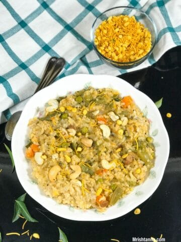 A plate of bisi bele bath is on the table and topped with nuts and boondi
