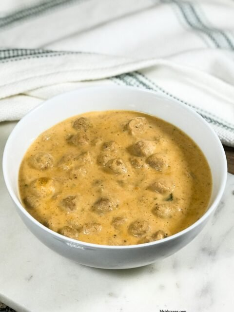 A bowl of meal maker curry is on the white serving tray