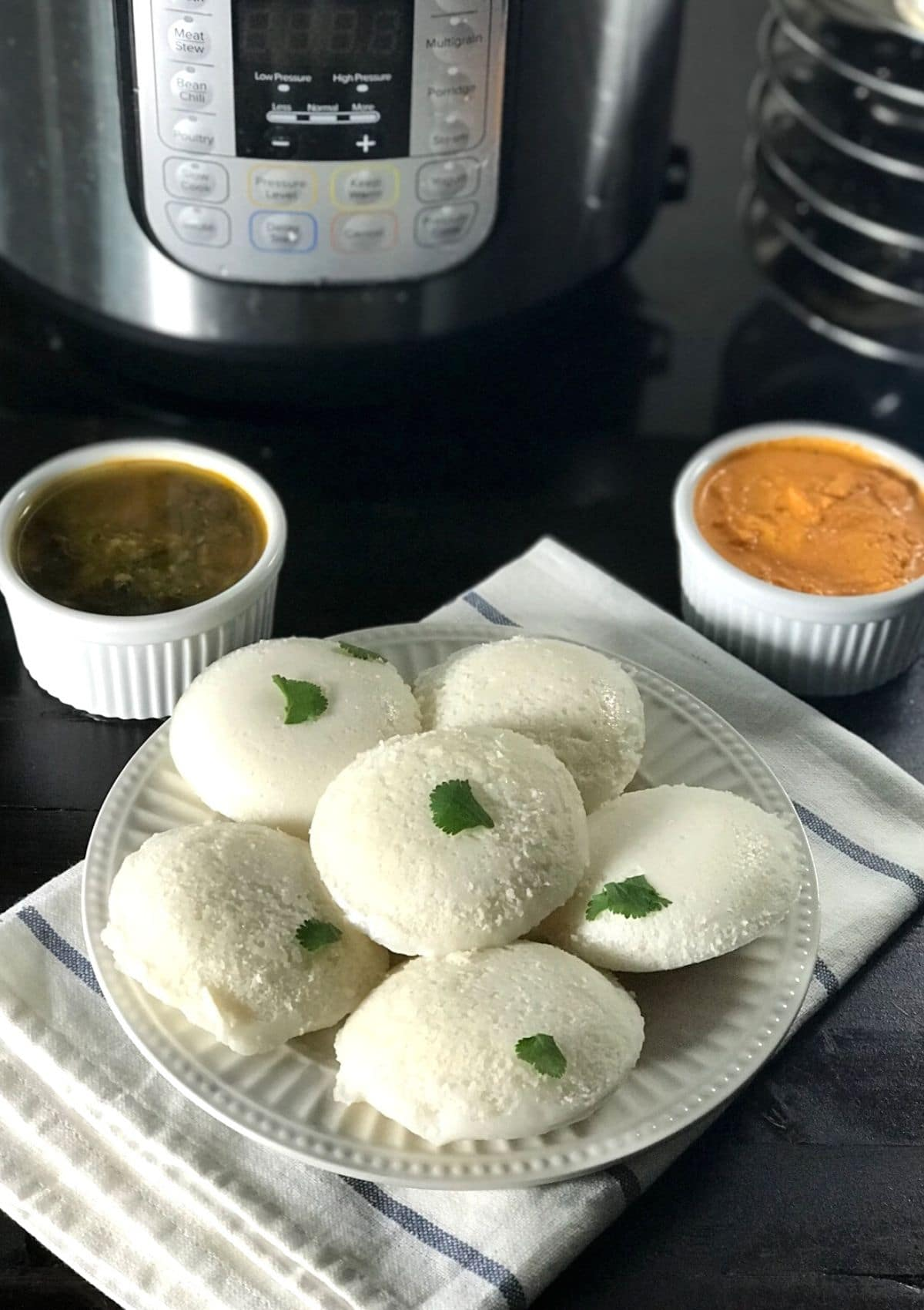 A plate with idli and bowl of chutney