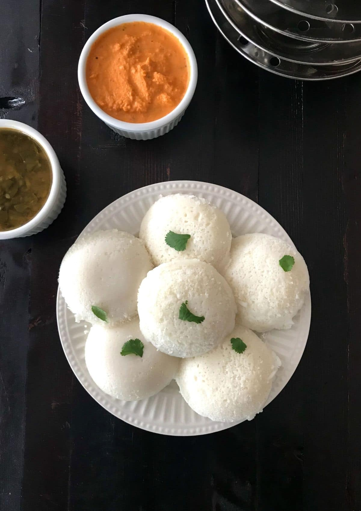 A plate with idli and cup of chutney