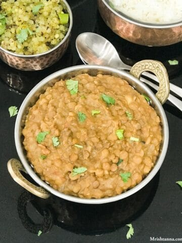 A bowl is filled with lentil curry and served on the black tray