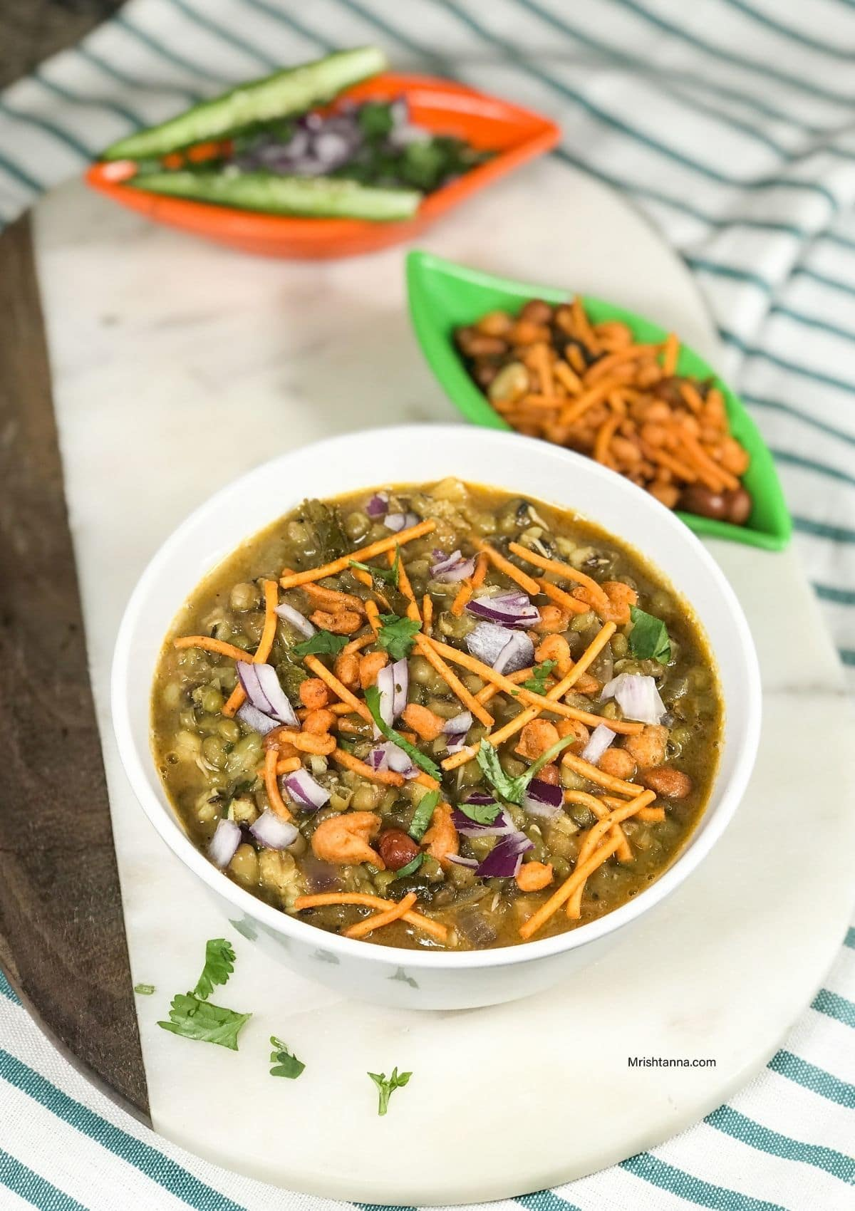 A bowl is filled with misal curry and topped with onions and fried mixture