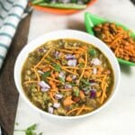 A bowl with misal masala and topped with red chopped onions