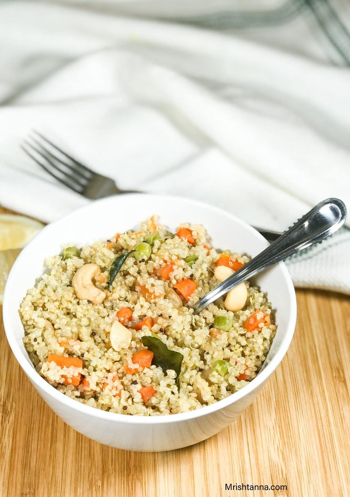 A bowl of quinoa upma with spoon inserted