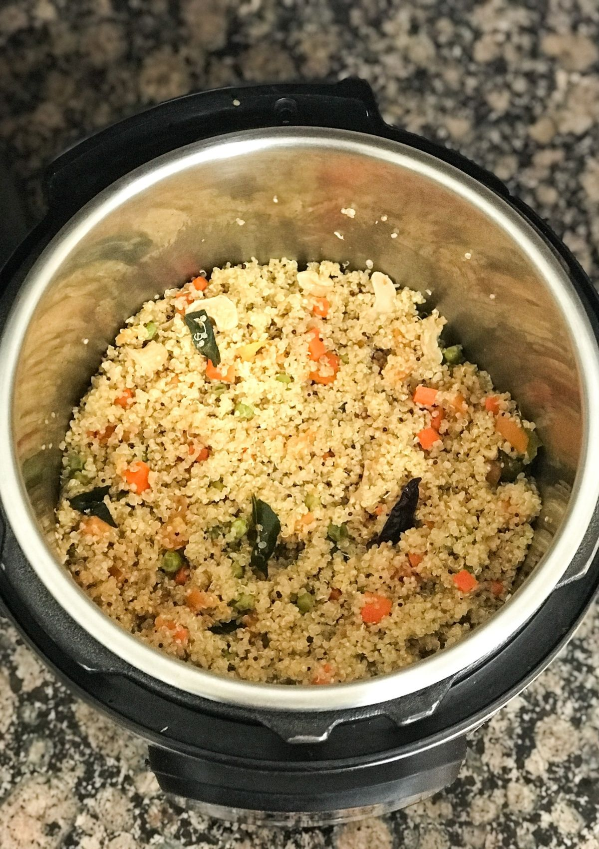 An instant pot with quinoa upma and topped with nuts
