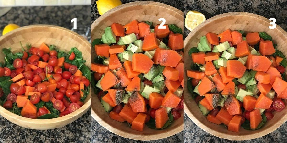 A big bowl of papaya, tomatoes, avocados and spinach blend is on the black surface