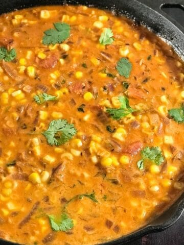 A cast iron pan with corn curry and topped with cilantro