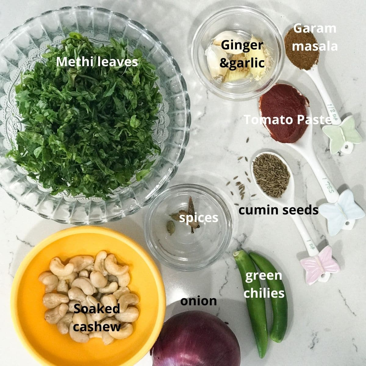 Many bowls are filled with ingredients for curry like methi leaves, soaked cashews, spices, and onion