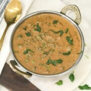 methi matar malai curry is served on the copper bowl and placed on the white table