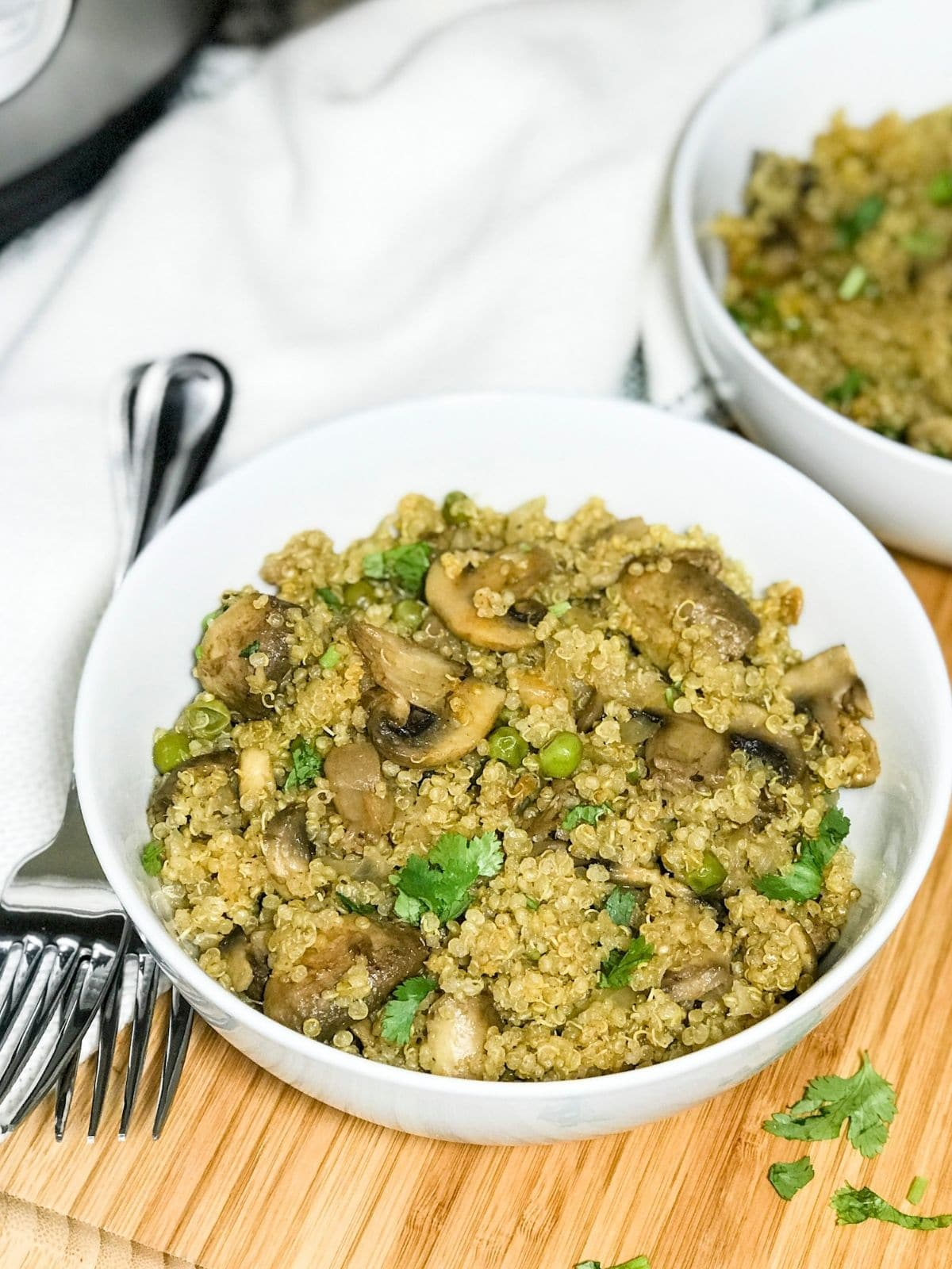 A bowl is filled with mushroom quinoa and topped with cilantro