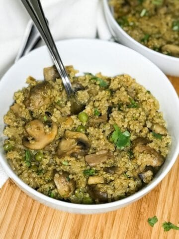 A bowl is with mushroom quinoa is on the table