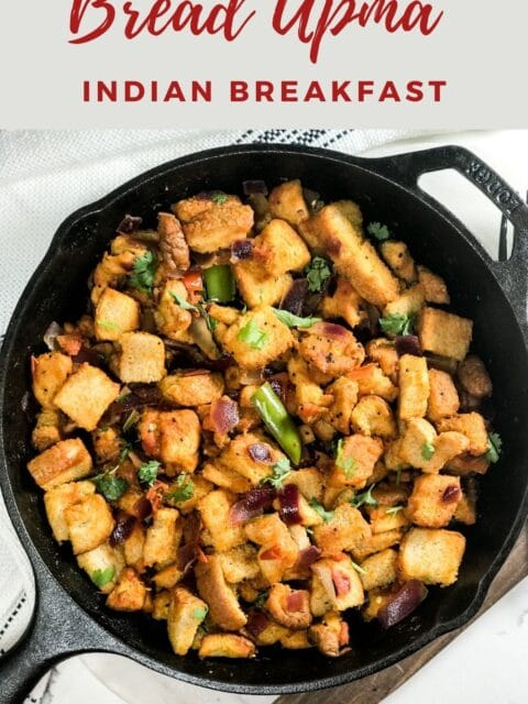 A cast iron pan is filled with bread upma and is on the white surface.
