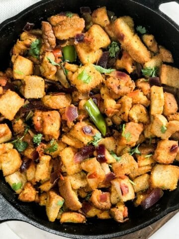 A cast iron pan is with bread upma