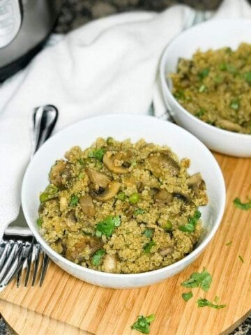 A bowl is with mushroom quinoa and placed on the wooden serving tray