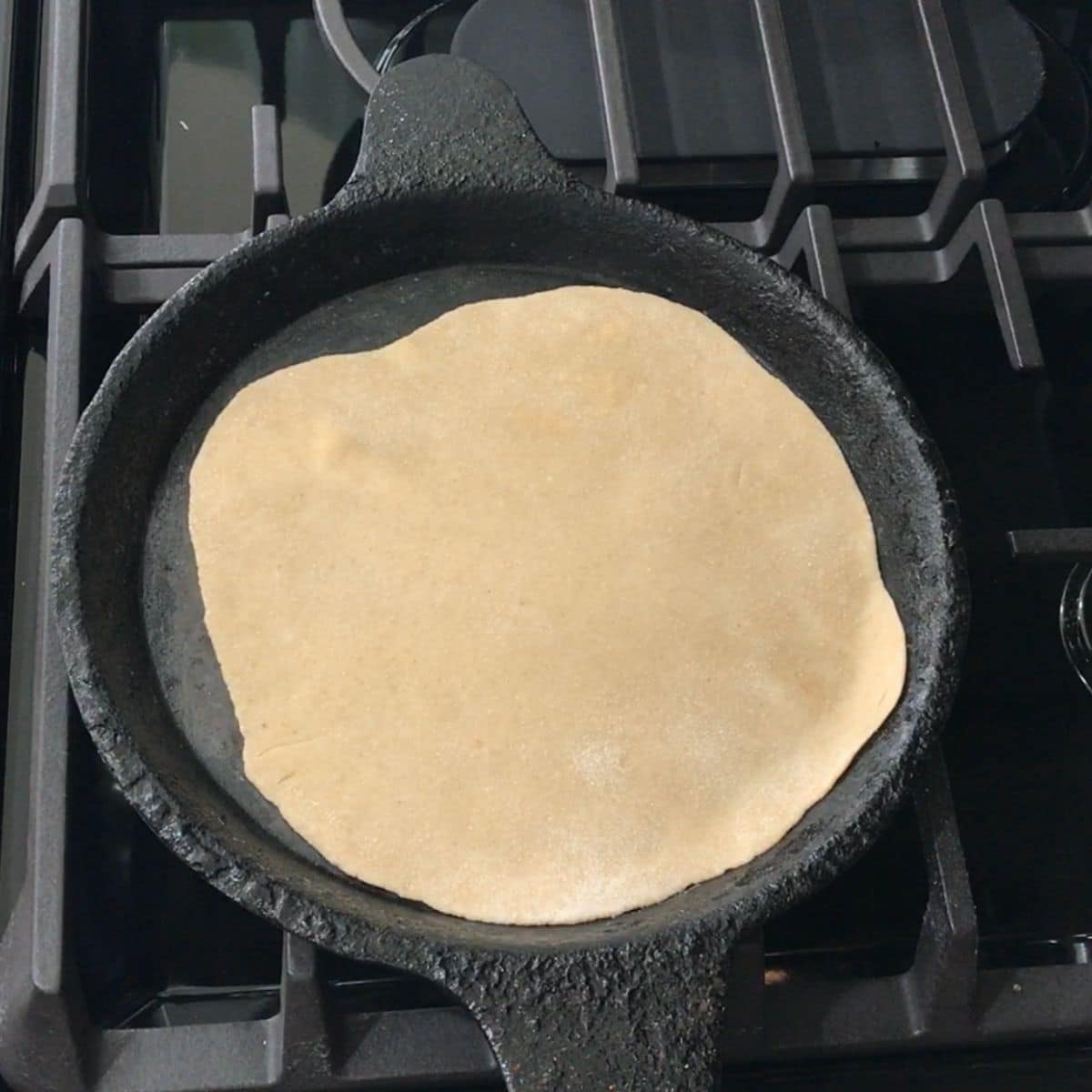 A phulka roti is placed on the tawa over the heat