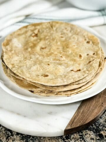 Phulka roti is stacked on the white plate and on the serving tray