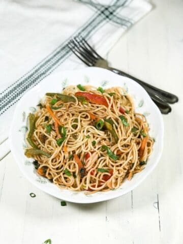 A plate is with hakka noodles over the white table