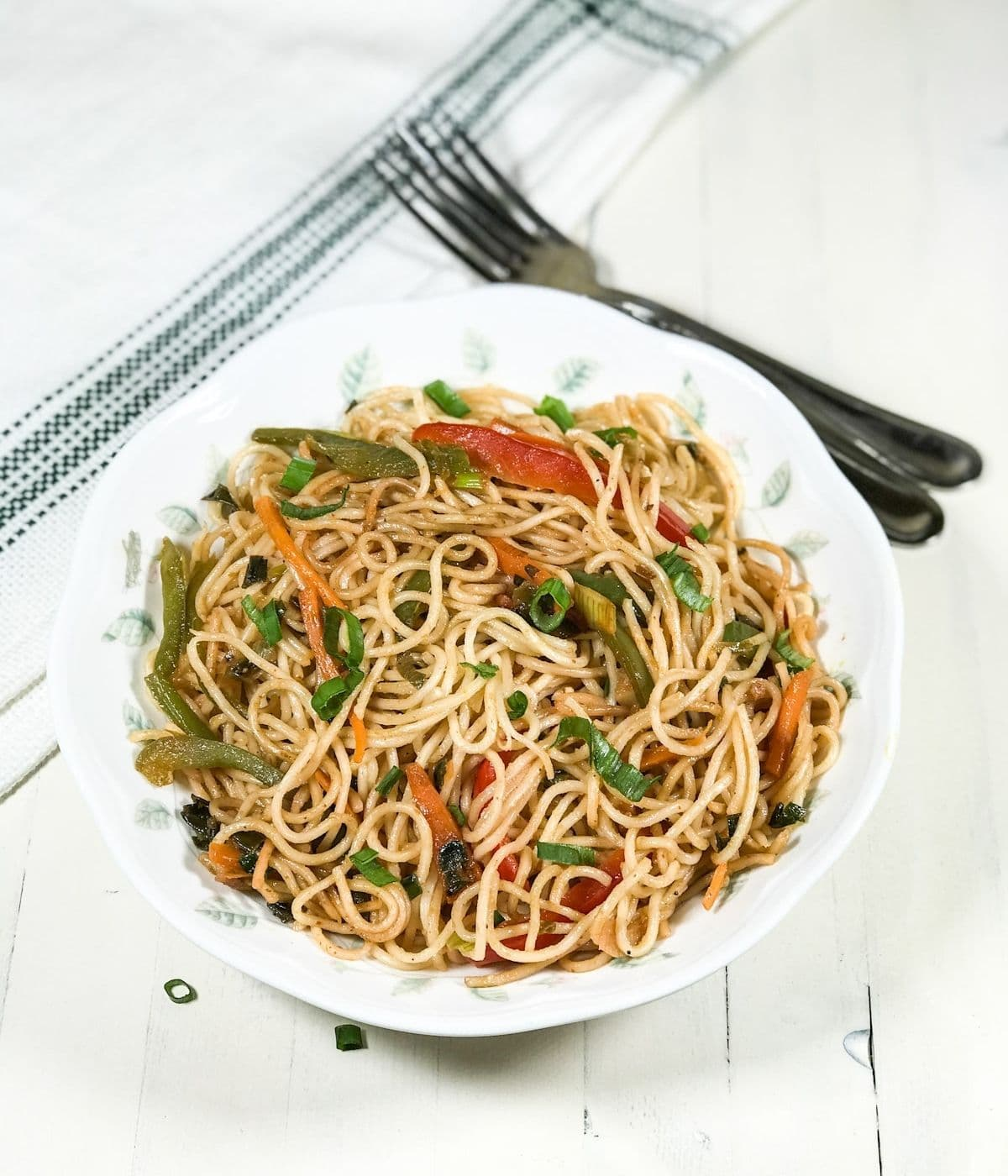 A plate with hakka noodles and topped with spring onions on the table