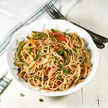 A plate is filled with vegetable hakka noodles and placed on the white table