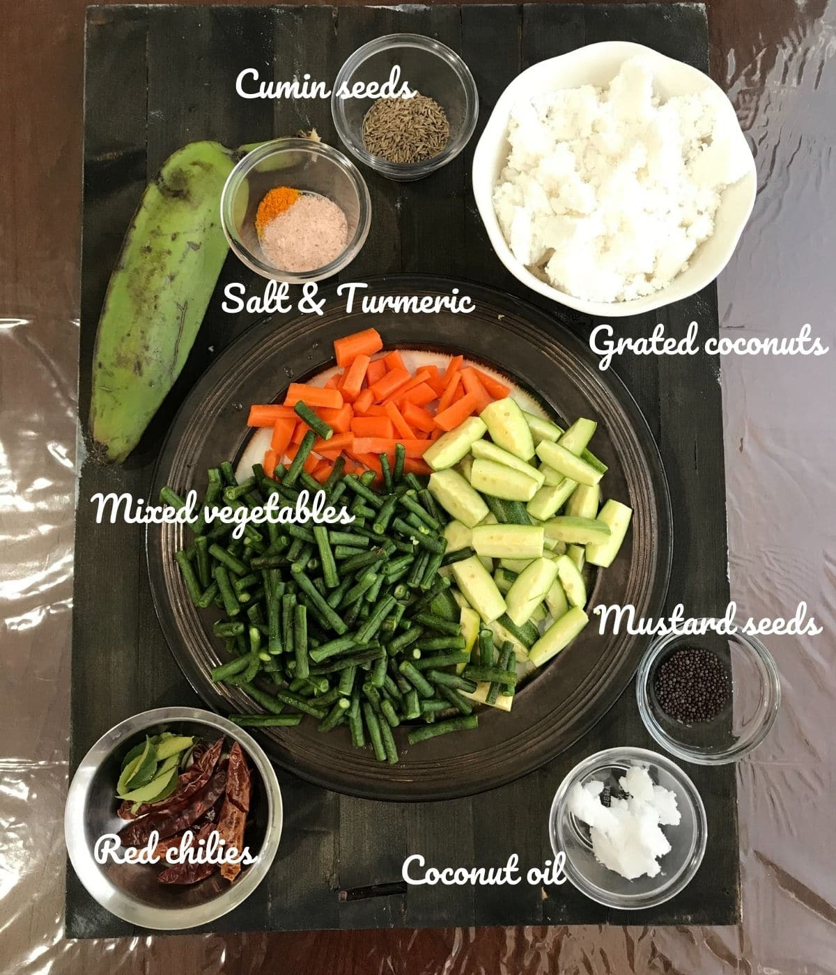 A board is filled with vegetables, spices, and grated coconuts