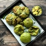 A tray is filled with Palak Puri and two kids are reaching out to take those puris