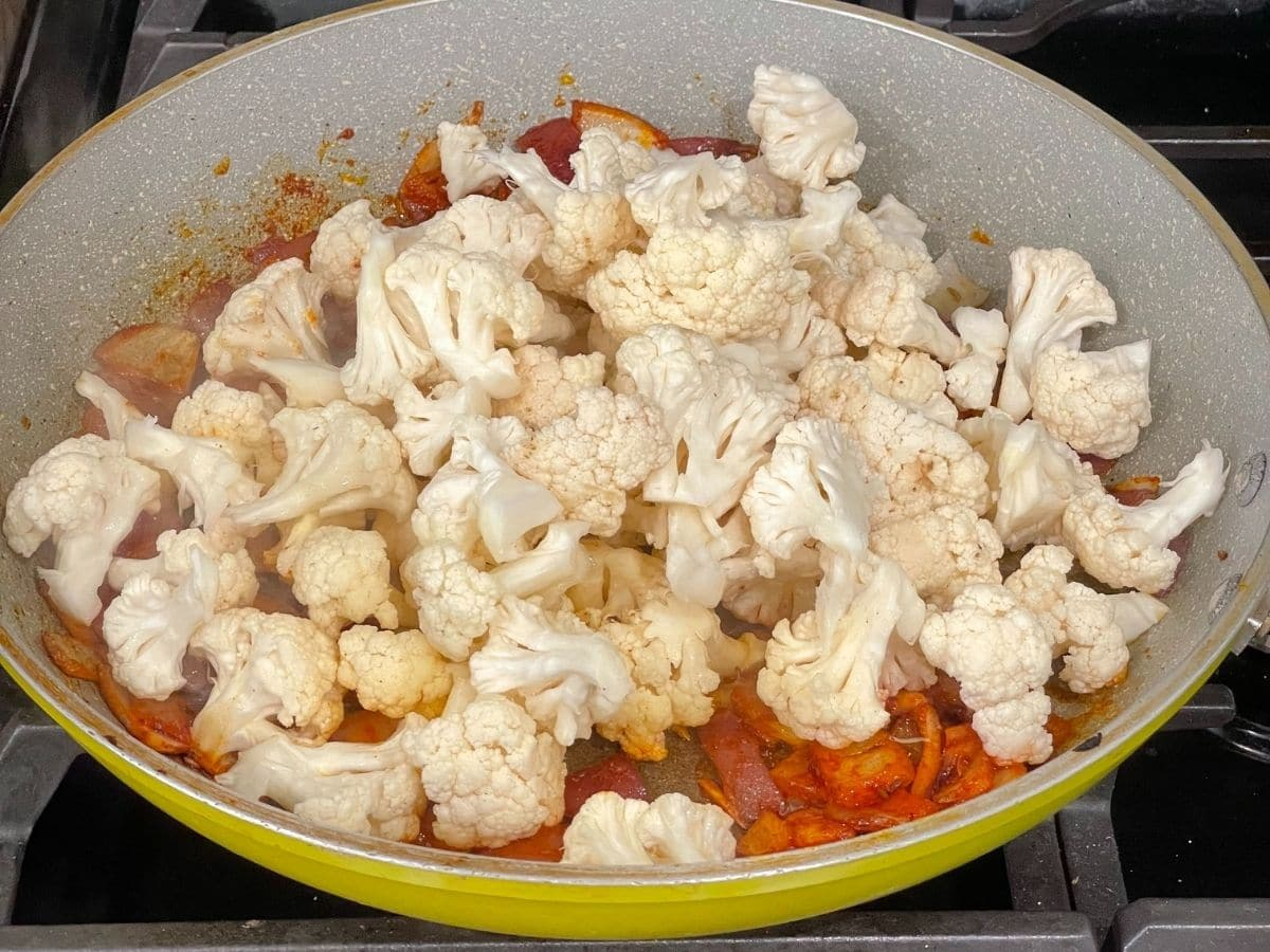 A pan is with spices and cauliflower and its on the heat