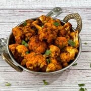 A bowl of cauliflower sabzi is on the white table