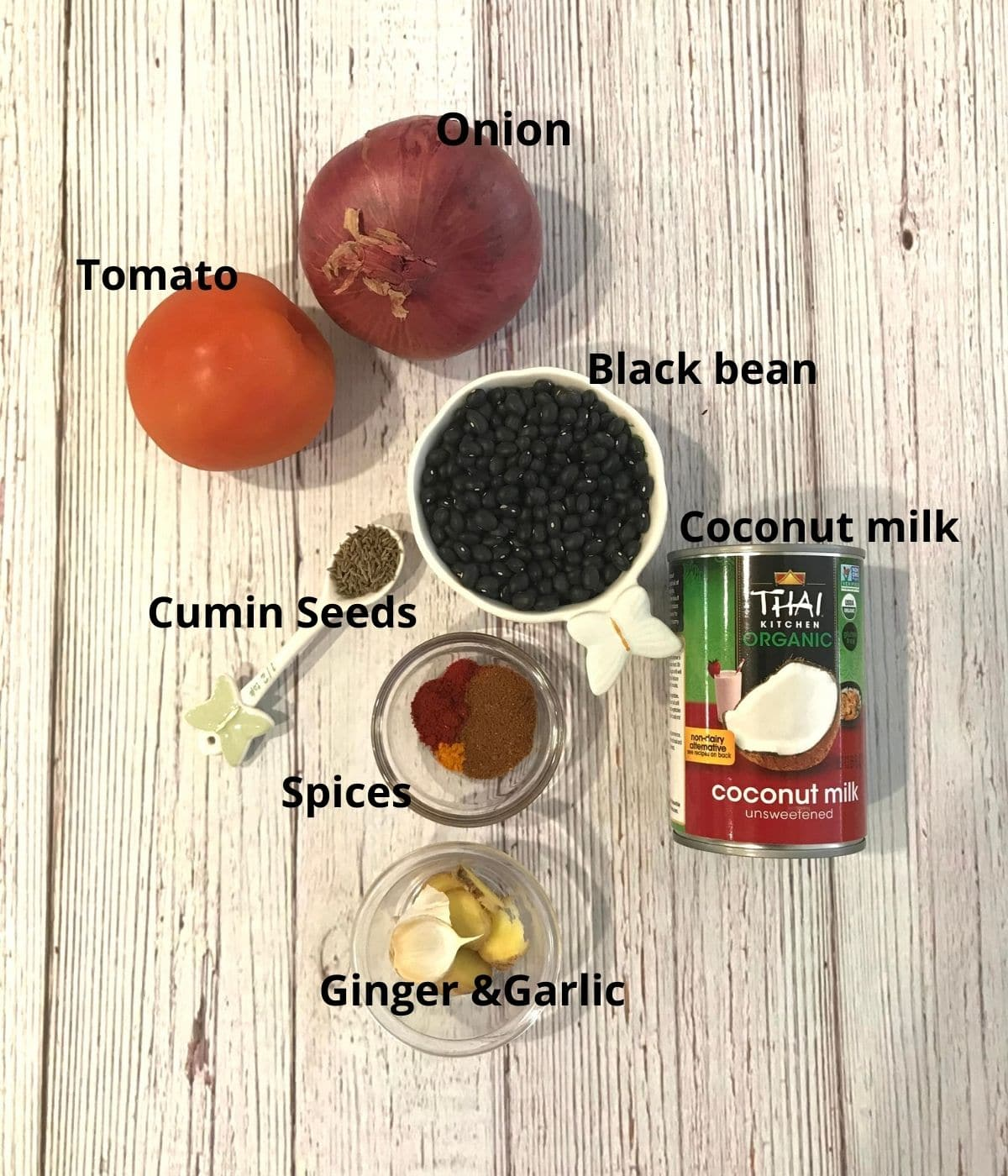 A table is filled with black bean, tomatoes, onion, spices for black bean curry