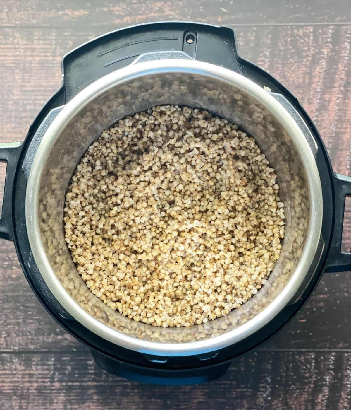 An instant pot is filled with cooked sorghum millet