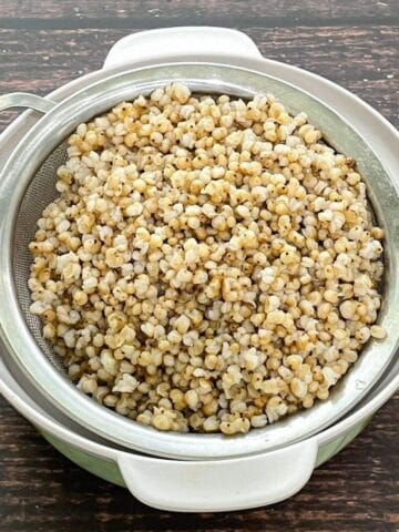 A strainer is filled with cooked sorghum on the table