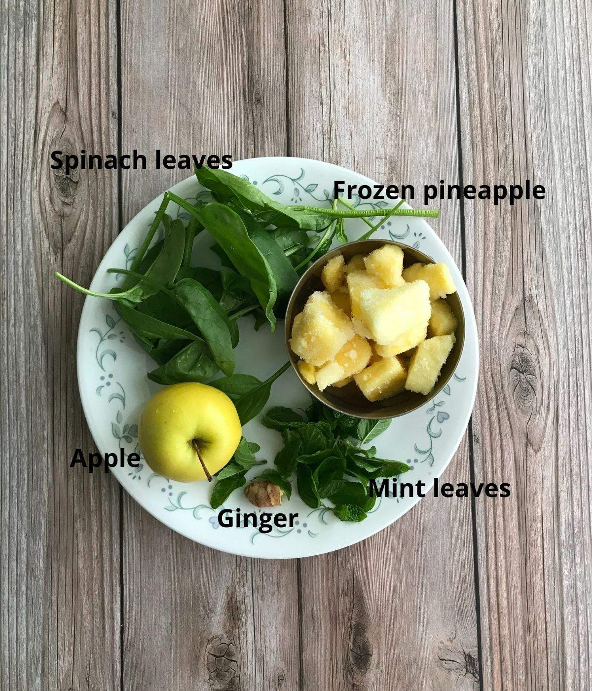 A plate is with spinach, apple, pineapple for spinach smoothie