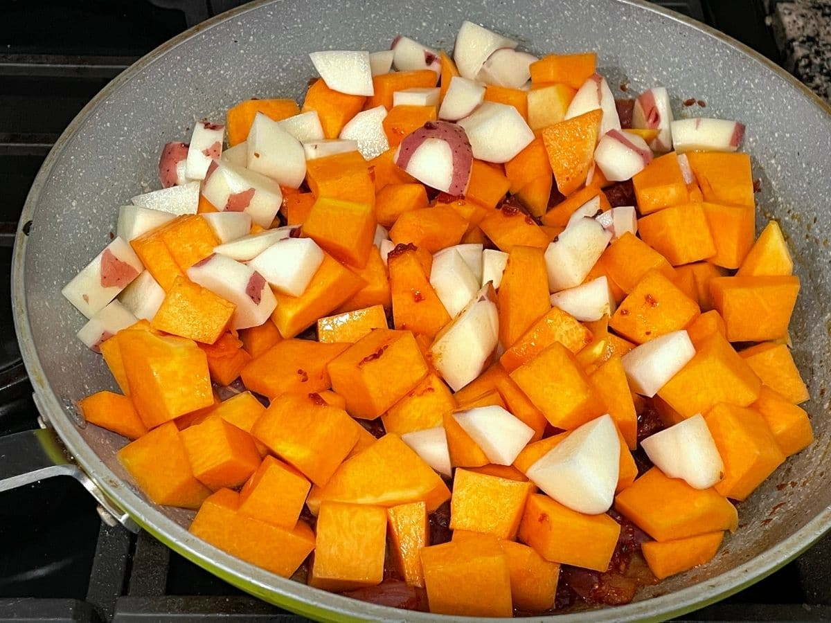 A pan is filled with cubed potatoes and pumpkins over the heat.