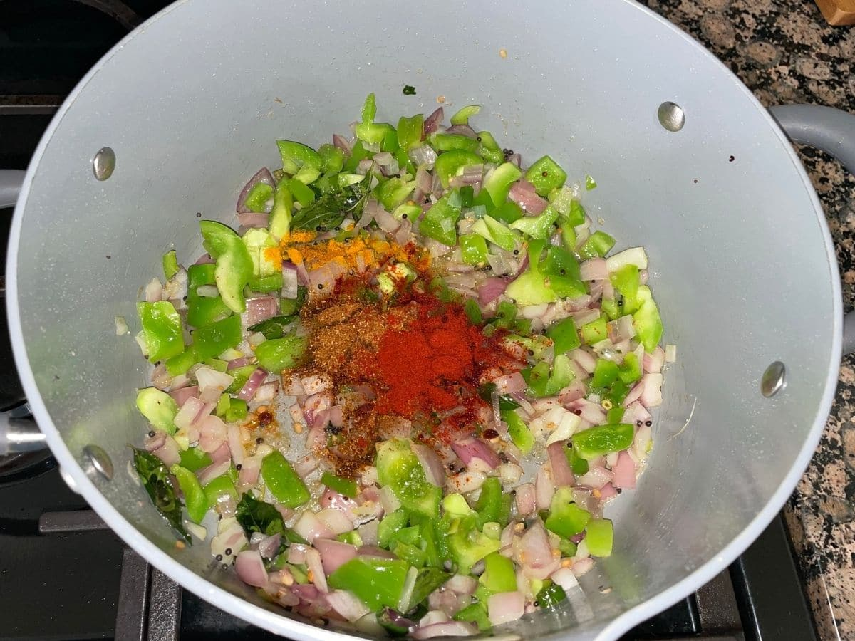 A pot is with spices and vegetables over the heat