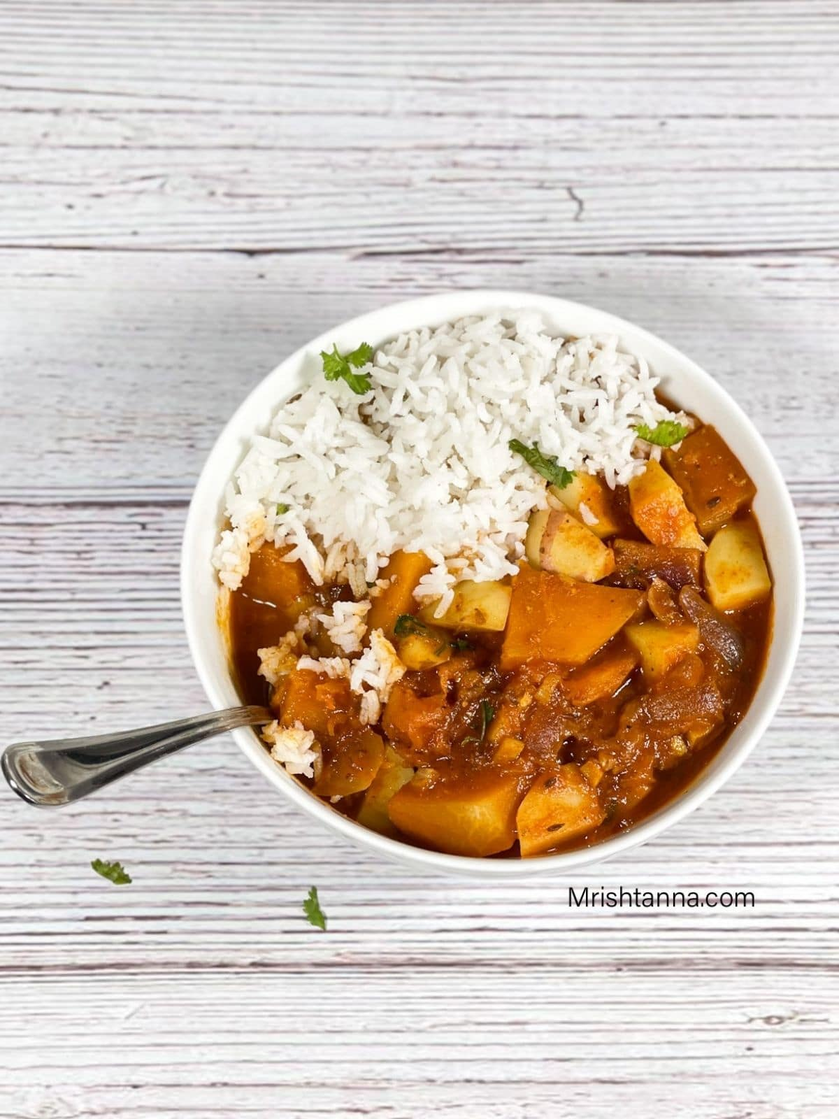 A bowl is with pumkin curry and rice with a spoon inside place on the table.