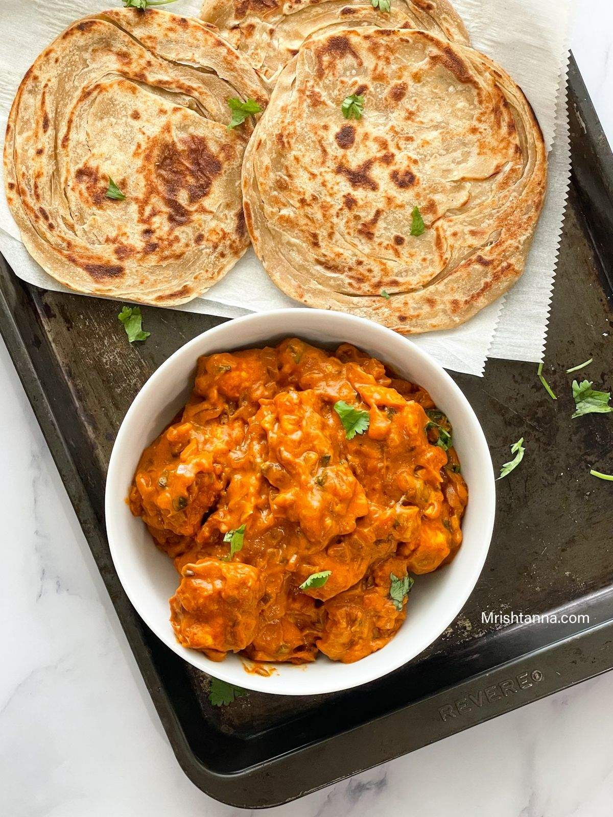 A bowl is filled with tofu butter chicken curry and placed on the baking tray along with paratha.