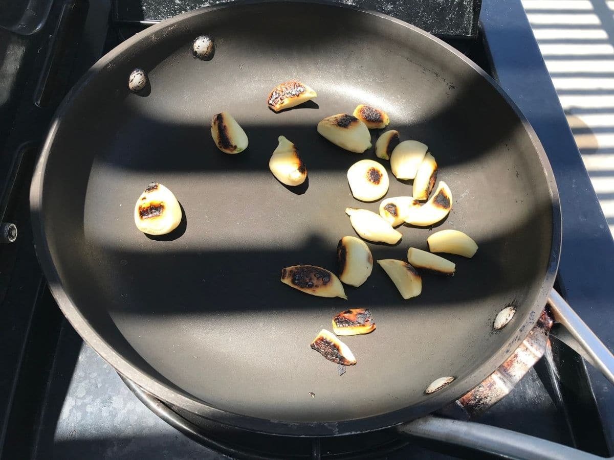 A pan is with garlic cloves over the heat