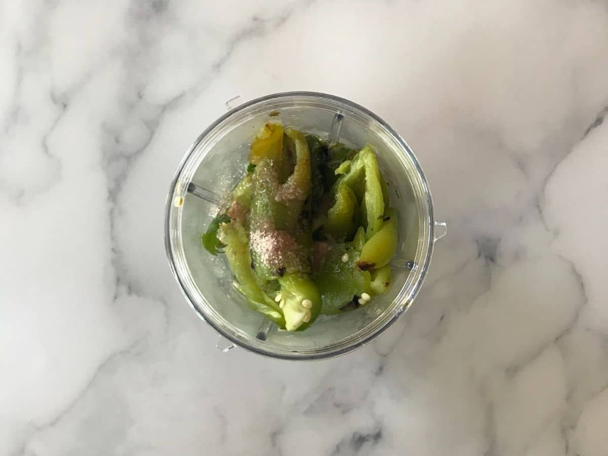 Roasted jalapeno, garlic, olive oil and cilantro is placed inside the blender.
