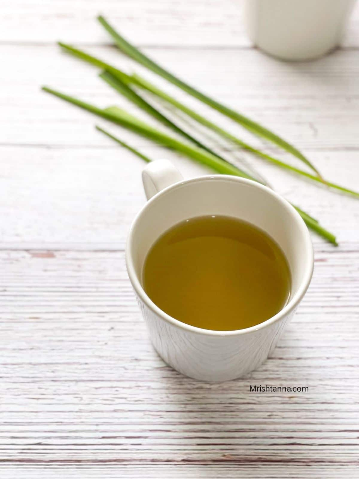 A cup of lemongrass tea is on the table